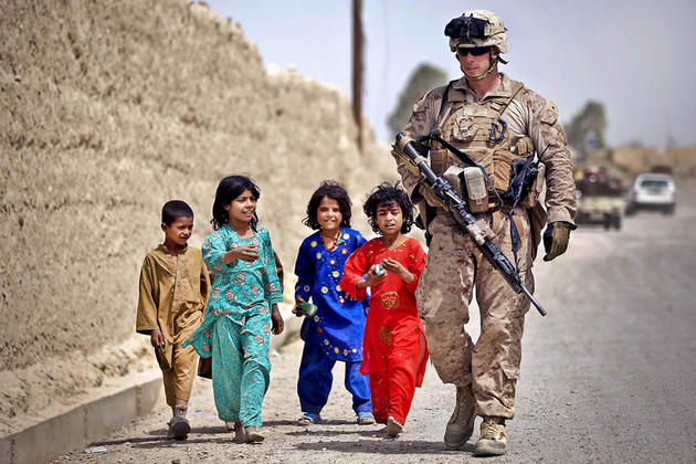 A US soldier walks with Afghanistan kids