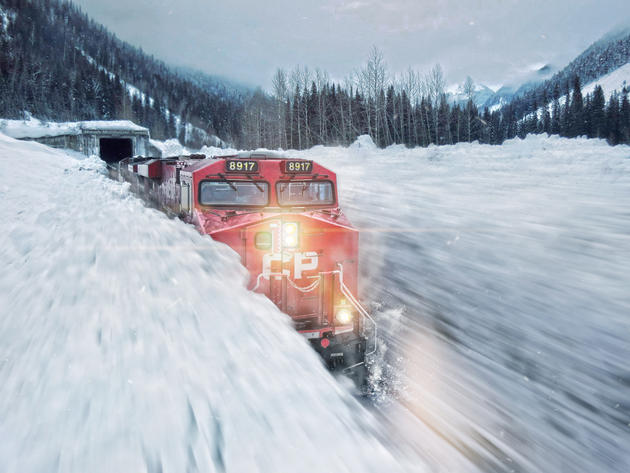 Canadian Pacific Railway train moving through avalanche debris in Glacier National Park, Canada