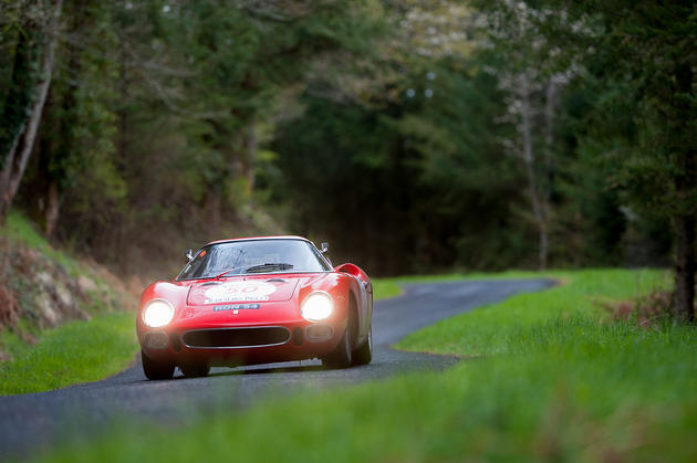 Ferrari 250 racing down a road in the country side