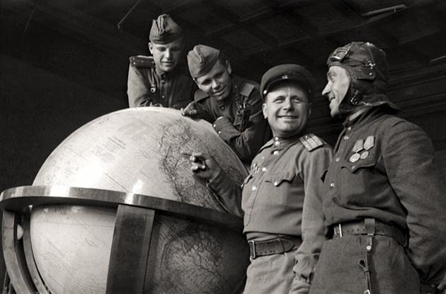 Soviet Soldiers standing next to Hitlers Globe