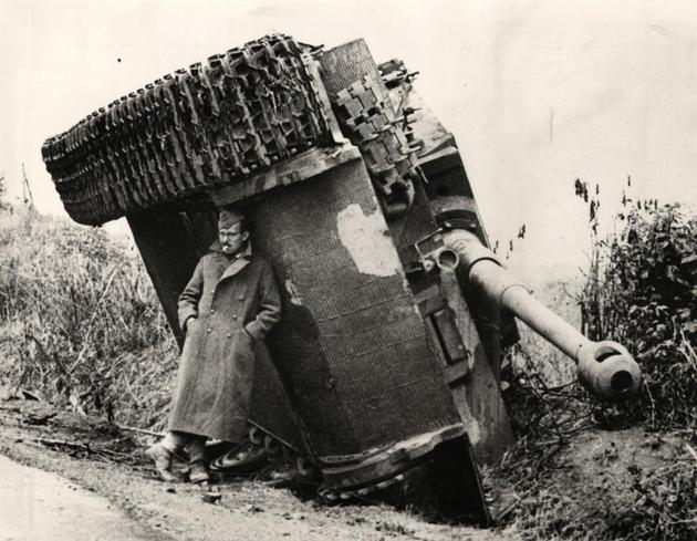 American soldier hiding from rain under a overturned  tiger tank