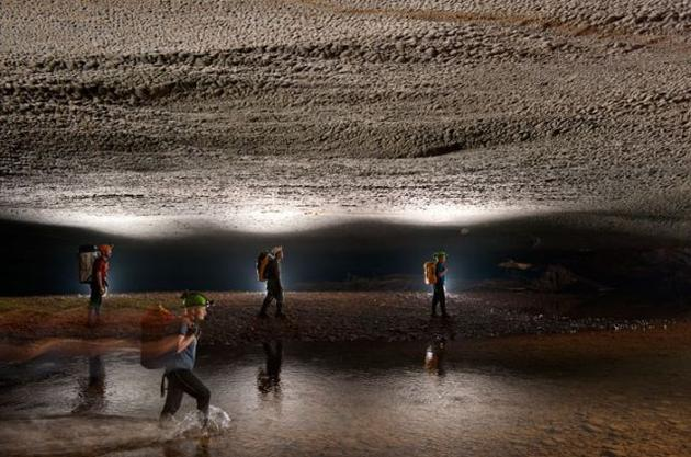 Scientists venturing under the low ceiling of the cave